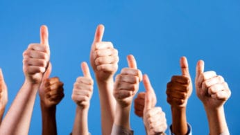 Many multiracial hands give group thumbs up of approval